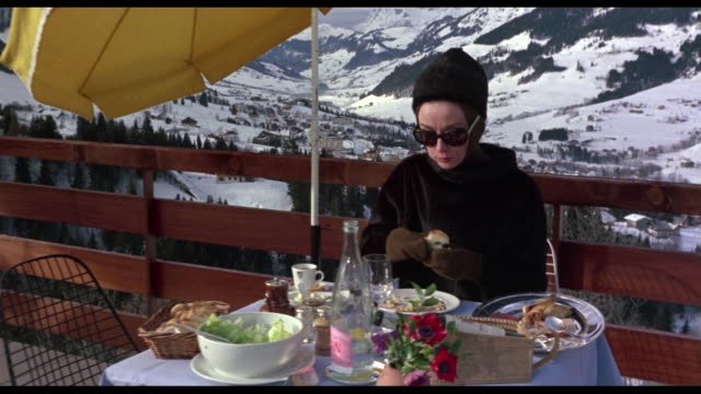 1963 Camera pans the French Alps before coming to rest outside at a mountaintop restaurant, Audrey Hepburn sitting at table