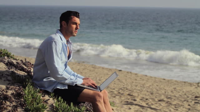 w/s camera pans to male on laptop on beach - fully unbuttoned stock videos & royalty-free footage