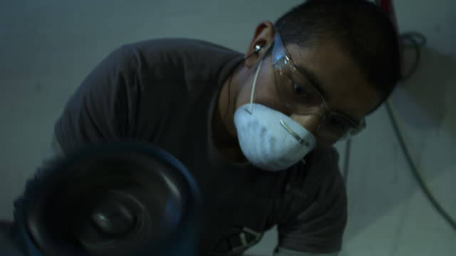 camera pans up and down on medium shot of man buffing a beam of metal. - solo un uomo di età media video stock e b–roll
