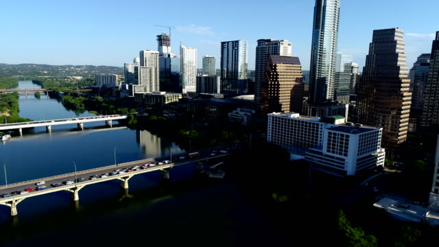 vídeos de stock e filmes b-roll de camera pans up to reflections of bridges and buildings and town lake on austin texas skyline cityscape aerial drone view morning sunshine - town