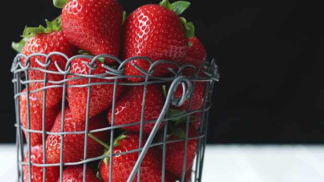 camera pans up to reveal close-up of strawberries in a wire basket against a black background - juicy stock videos & royalty-free footage