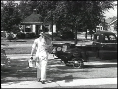 ws camera pans with 1952 chevrolet panel van as it drives down road / dissolve to painter carrying his ladder out to his chevy pickup truck parked at... - シボレー点の映像素材/bロール