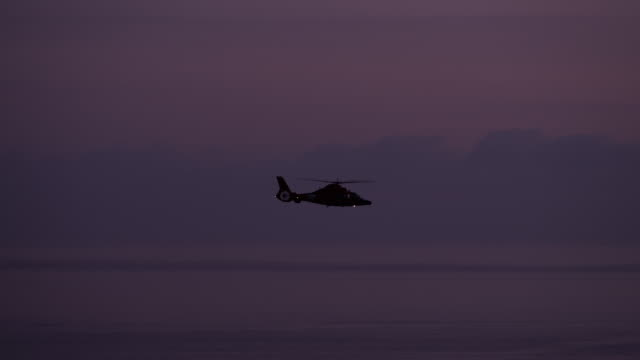 Camera pans with Coastguard helicopter, dusk, pink skies and low cloud bank in background