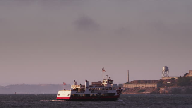 Camera pans with ferry as it motors past Alcatraz Island and exits frame.