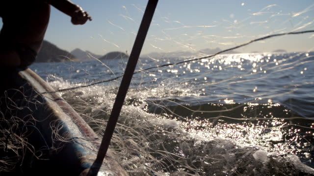 camera pans with fishing net as it unfurls into the sea from fisherman's hands in slow motion - cast member stock videos & royalty-free footage