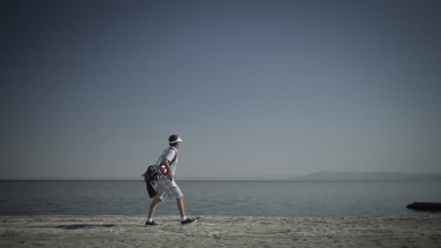 camera pans with golfer as he walks along shore of salton sea. - golf bag stock videos & royalty-free footage