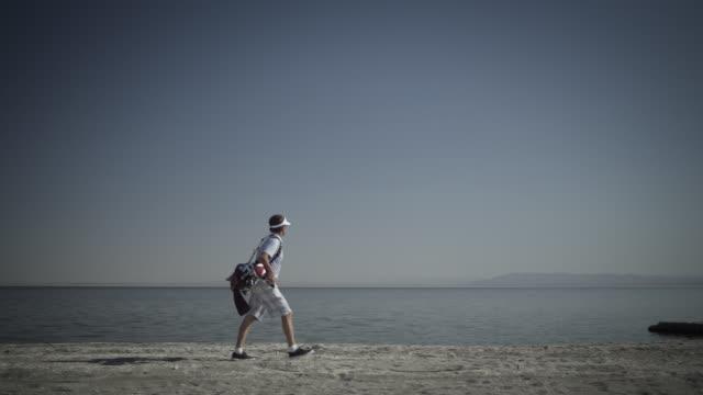 vídeos de stock, filmes e b-roll de camera pans with golfer as he walks along shore of salton sea. - bolsa de golfe