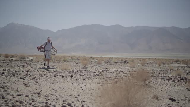 camera pans with golfer as he walks by, mountains in background. - schiebermütze stock-videos und b-roll-filmmaterial