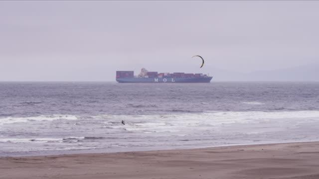 camera pans with kiteboarder sailing across whitewater at ocean beach, container ship in background - kiteboarding stock videos & royalty-free footage