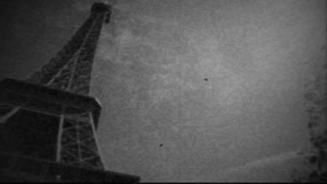 camera pans with lens flare to reveal the eiffel tower in vintage black and white film footage. - french culture stock videos & royalty-free footage