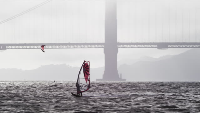 Camera pans with windsurfer sailing on San Francisco Bay near Crissy Field, Golden Gate Bridge north tower, cruise ship in background. Windsurfer turns and heads back out.