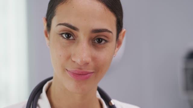 vídeos de stock, filmes e b-roll de camera paralax view of young latina doctor smiling indoors medical room - expressão facial