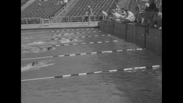 Camera person signals 1 / swimmers dive into pool for race during Olympic trials / VS race / VS three swimmers stand in pool / VS another race / two...