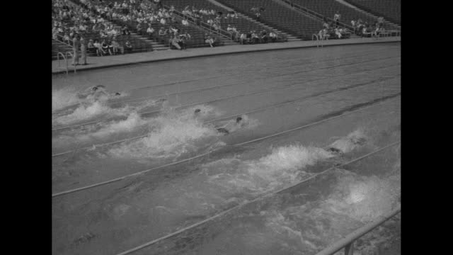 Camera person signals 1 / VS swimmers dive off side of pool race in Olympic trials competition / happy swimmer smiles after finishing well / two...