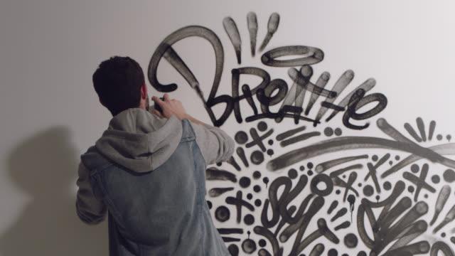 stockvideo's en b-roll-footage met slo mo. camera pulls back as graffiti artist spraypaints white studio wall with intricate words and designs. - ondertekenen schrijven