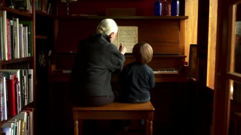 vídeos y material grabado en eventos de stock de camera pulls back slowly on grandmother and grandson playing piano. - nieto
