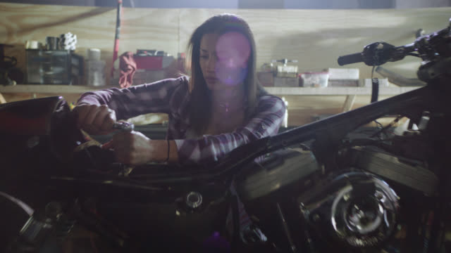 vídeos de stock e filmes b-roll de camera pushes in on female mechanic working on motorcycle with ratcheting socket wrench in garage. - mecânico