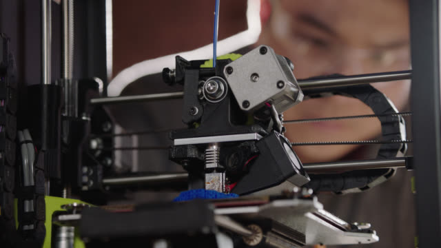 CU. Camera racks focus as creative engineer inspects 3D printer and takes notes in modern technological workplace.