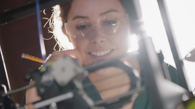 vídeos de stock e filmes b-roll de cu. camera racks focus as creative female engineer inspects 3d printer and takes notes in modern technological workplace. - engenheiro