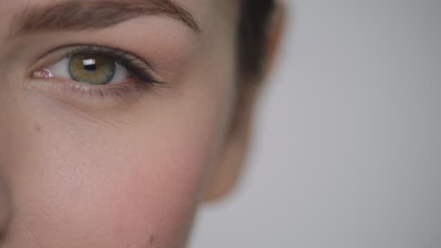 ecu slo mo. camera racks focus on woman's eye staring into camera. - eyesight stock videos & royalty-free footage