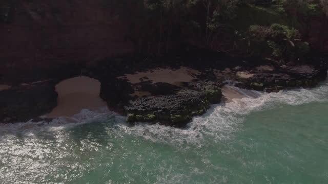 AERIAL. Camera rises over rocky beach as waves crash on island shore.