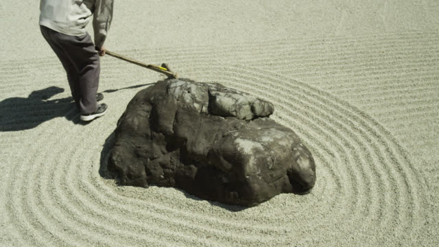 Camera rotates as man rakes gravel around rock in zen garden at Gyokudo art museum.