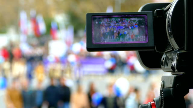 camera shoots a reportage about the demonstration