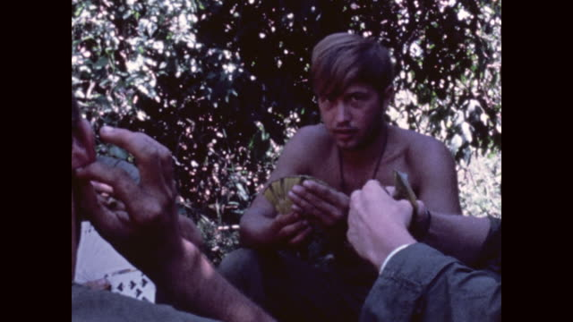 camera shows rucksack and m16 on the ground and then pans up to soldiers of the 1st cavalry division playing cards closeup of faces - m16 stock videos & royalty-free footage