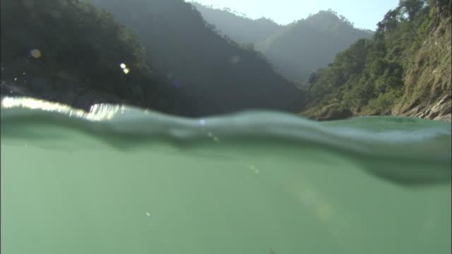 vídeos de stock, filmes e b-roll de camera sinks below river surface as water rushes towards camera, rishikesh, india available in hd. - rishikesh