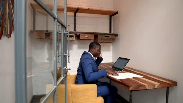 vidéos et rushes de diapositives d'appareil-photo pour révéler l'homme d'affaires africain travaillant sur le desking chaud d'ordinateur portatif - hot desking