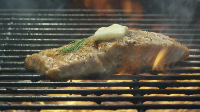 camera slowly reveals a seasoned salmon steak filet with dill and butter cooking over a bed of coals on a barbecue grill - filleted stock videos & royalty-free footage