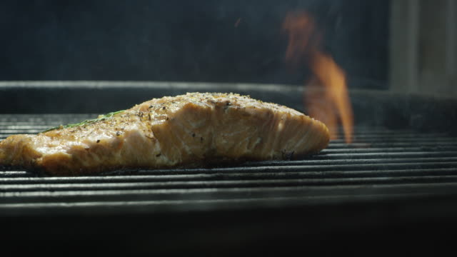 camera slowly reveals a seasoned salmon steak filet with dill cooking over a bed of coals on a barbecue grill - grilled stock videos and b-roll footage