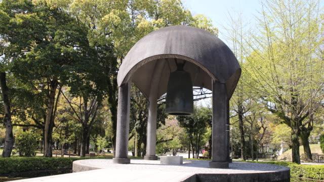 vidéos et rushes de a camera tilt down showing the peace bell a monument located next to the children's peace monument in the memorial park's complex - arme de destruction massive