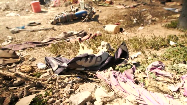 camera tilt down to a tattered isil flag surrounded by debris in baghouz, syria on march 23, 2019. - flag stock videos & royalty-free footage