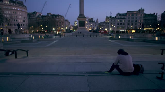 camera tilt establishing shot of a man sitting on steps in trafalgar square during the covid-19 pandemic in london. - healthcare and medicine or illness or food and drink or fitness or exercise or wellbeing stock videos & royalty-free footage