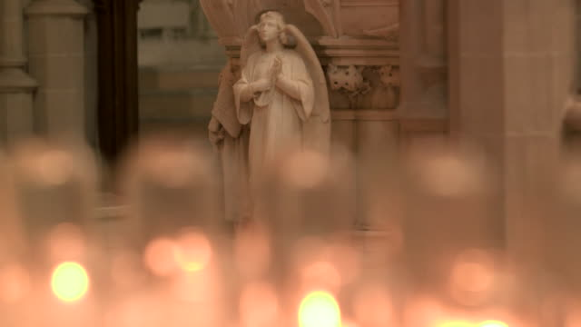 camera tilt up from defocused prayer candles to a statue of an angel inside of saint paul cathedral in pittsburgh pennsylvania on august 15 2018 - religion or spirituality bildbanksvideor och videomaterial från bakom kulisserna