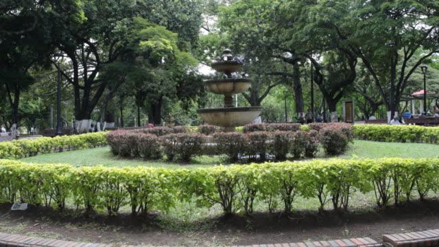 vídeos de stock, filmes e b-roll de a camera tilt up on a round garden with a fountain in the middle - jardim clássico