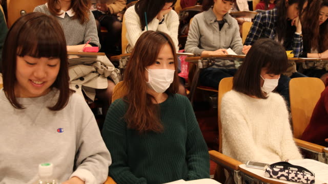 A camera tilt up showing female students sitting in a big lecture two girls in the front are wearing white protective masks