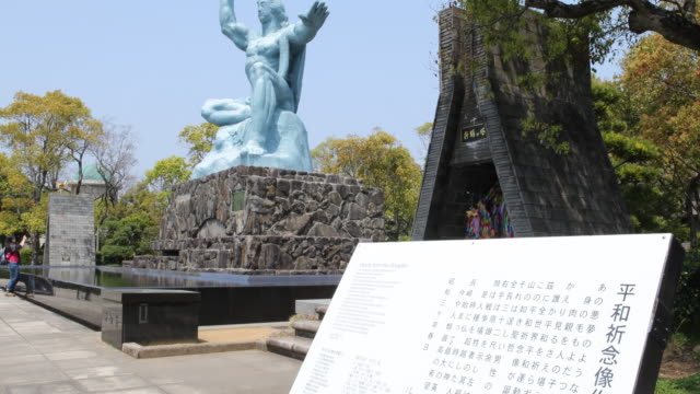 vidéos et rushes de camera tilt up, showing information plaque and the peace statue, a sculpture 10 meters tall made by seibo kitamura, dedicated for the victims of the... - retombée radioactive