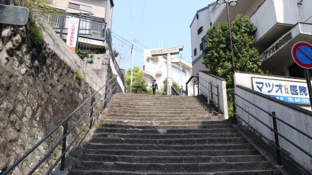 camera tilt up, showing young people going down the stone stairs and the one-legged torii at the top, a standing remain of the sanno shrine which... - 大量破壊兵器点の映像素材/bロール