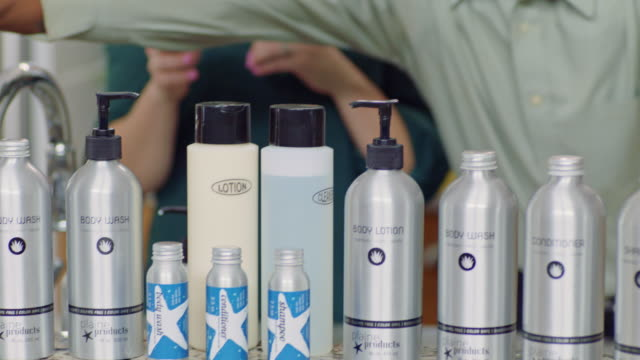 camera tilts down and pans left from infomercial host to reveal a variety of eco-friendly body and hair care bottles from plaine products. - hair conditioner stock videos and b-roll footage