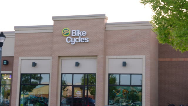camera tilts down on brick storefront of bike shop in shopping center - centro commerciale suburbano video stock e b–roll
