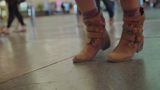 vídeos y material grabado en eventos de stock de camera tilts down to follow boot steps as hip young woman dances free in downtown las vegas. - calzado