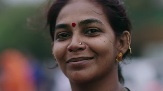 vidéos et rushes de cu slo mo. camera tilts up as proud woman looks at camera and smiles. - indien d'inde