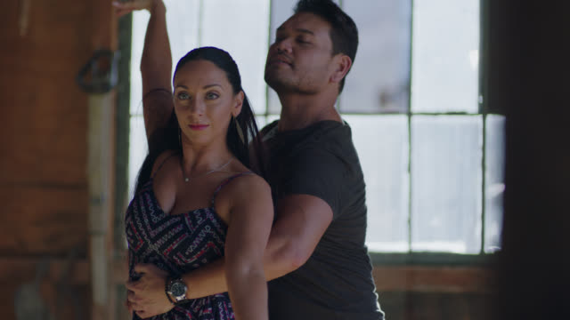 MED SLO MO. Camera tilts up as two ballroom dancers perform passionate routine in rustic wooden barn.