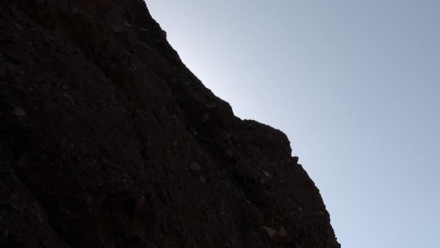 camera tilts up cliff to show climber cheering - 中年の男性だけ点の映像素材/bロール