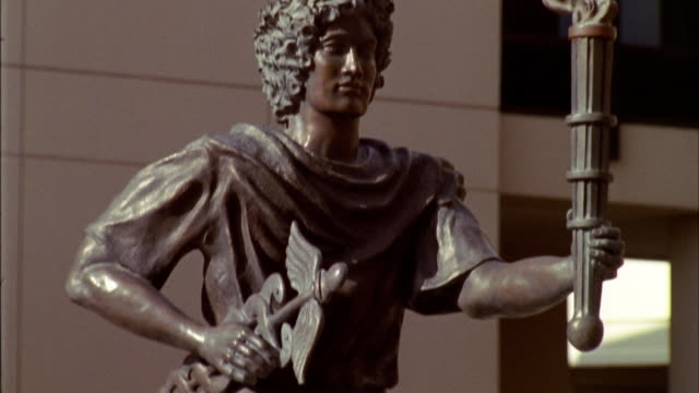 camera tilts up from a fountain featuring a bronze statue of the greek god mercury with torch and caduceus. - metal blend stock videos and b-roll footage