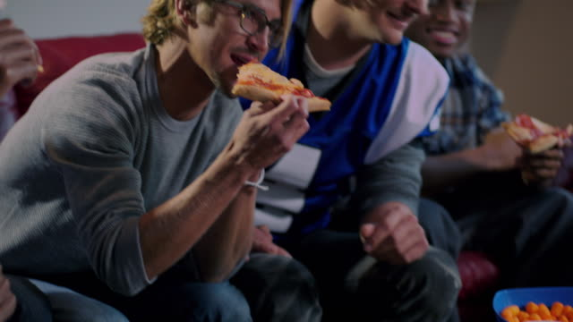 camera tilts up from pizza to group of young adult males watching sports on tv - pizza stock videos & royalty-free footage