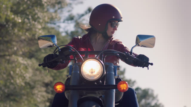 slo mo. camera tilts up from spinning tires on asphalt to woman on motorcycle riding with friends. - motorcycle biker stock videos & royalty-free footage