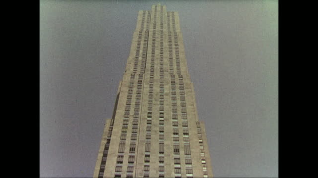 1937 camera tilts up the side of rockefeller center building in new york - rockefeller center video stock e b–roll